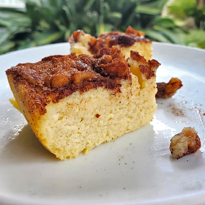 this is a coffee cake on a white plate with palm trees in the back. The cake is made with coconut flour and has a streusel topping with walnuts