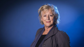 Maggie Steed in a grey suit against a blue background