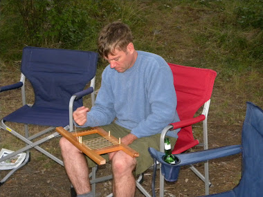 Caning canoe seats by the camp fire