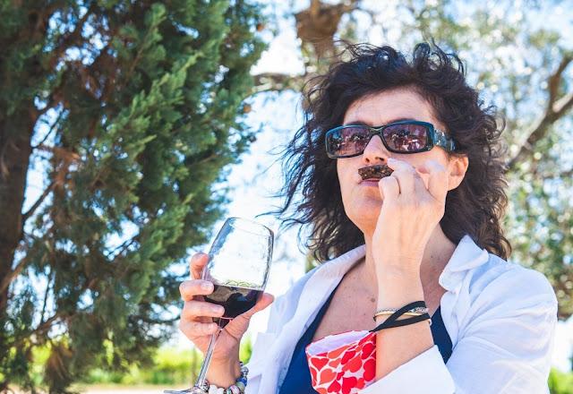 Donna con occhiali da sole e un calice di vino