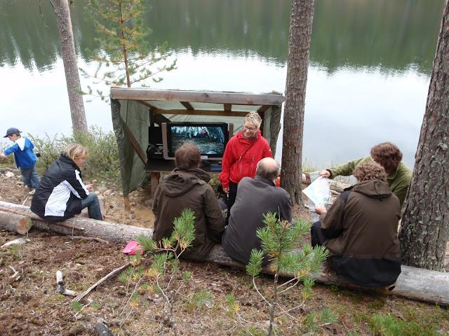Neljä ihmistä istuu ja katsoo kahta muuta ja telkkaria metsässä, taustalla lampi
