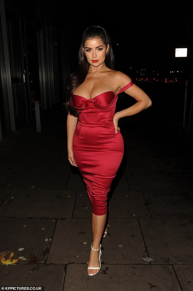 Demi Rose sets pulses racing as she shows off her fabulous curves in a plunging crimson gown while stepping out for Christmas bash