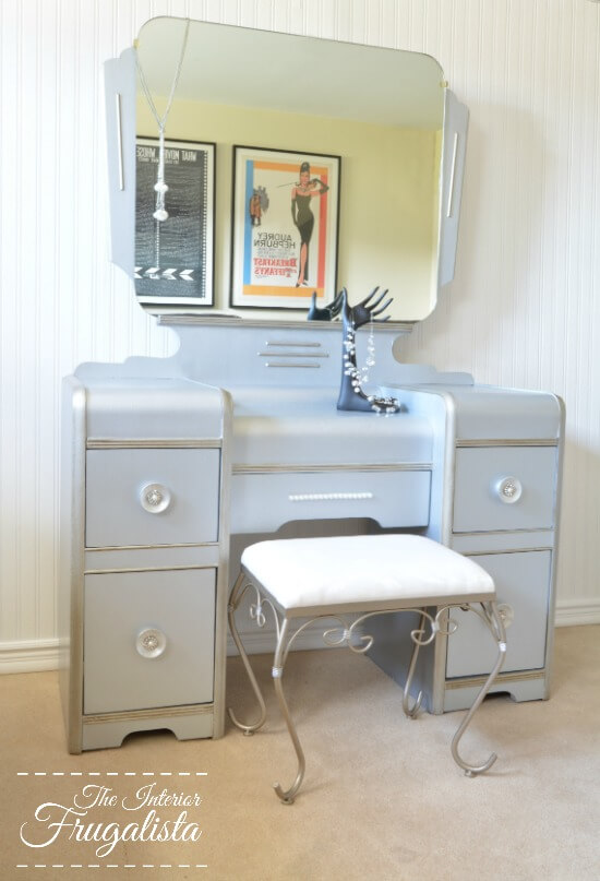 How to give a vintage waterfall vanity a drab to fab hollywood glam makeover with metallic paint, wrapping paper, and pearl embellished knobs.