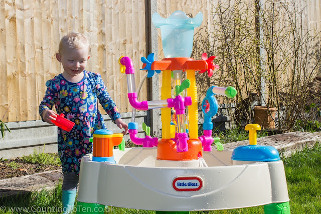 A toddler standing back and looking at the Little Tikes Fountain Factory Water Table