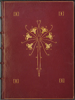 A red leather book cover stamped with floral elements in gold.