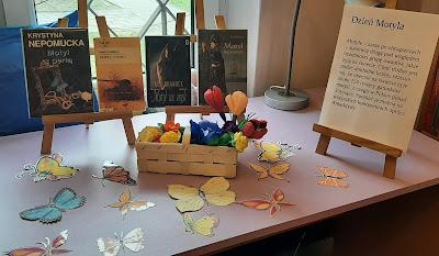 Na sztalugach cztery książki o motylach oraz napis Dzień motyla. Pod sztalugami motyle i kwiaty w wiklinowym koszyku