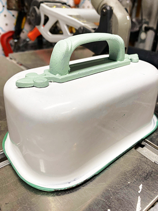 enamelware container with a green handle