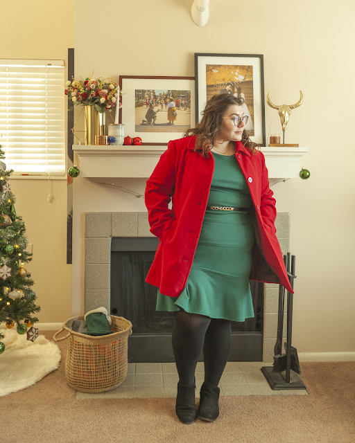 An outfit consisting of a green fluted knee length dress and a red coat.