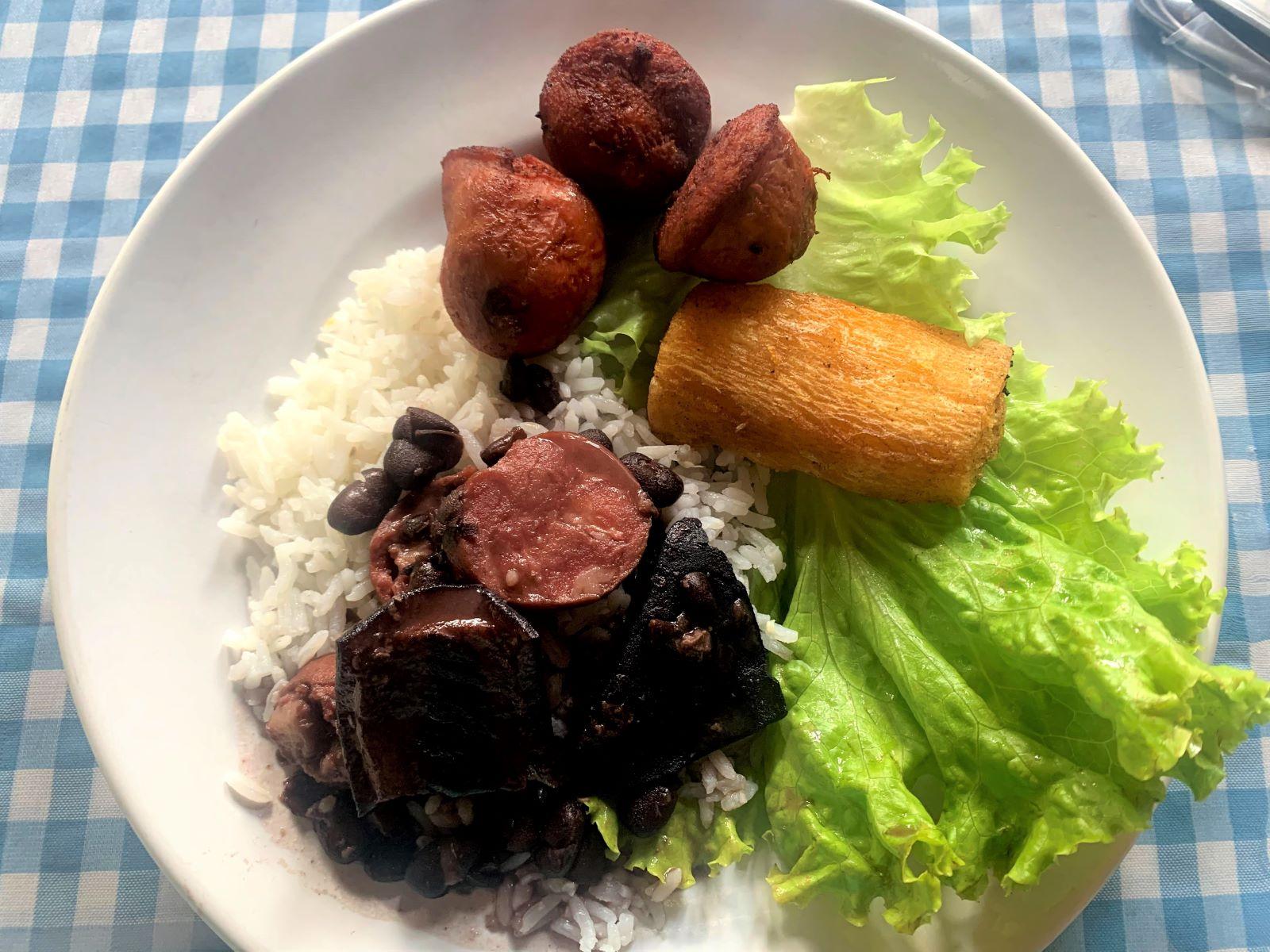 prato de comida com arroz, feijoada, mandioca frita, alface e linguiça