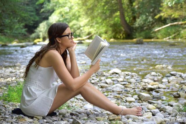 ảnh cô gái đang ngồi đọc sách bên dòng suối nhỏ