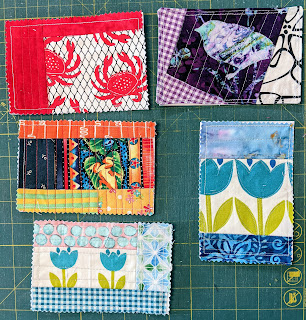 Postcards of colorful scraps rest on a green cutting board. The fabrics include a crab, bird, frog, and several tulips.
