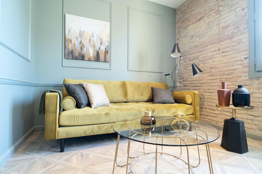 Salón moderno con pared azul con molduras de escayola y sofá dorado