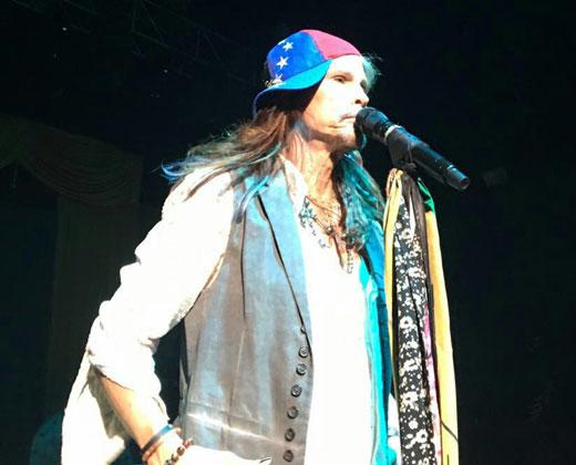Steven Tyler usa una gorra de Venezuela durante un concierto