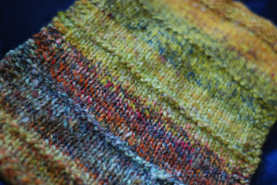handspun yarn combospin knitted swatch of orange, yellow, red and other colours of wool and other fibres