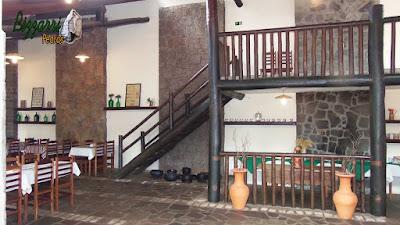 Parte interna do restaurante Recanto das Pedras com a parede de pedra, o piso de pedra com tijolo de demolição com o mezanino com eucalipto tratado com o corrimão e o guarda corpo de madeira.