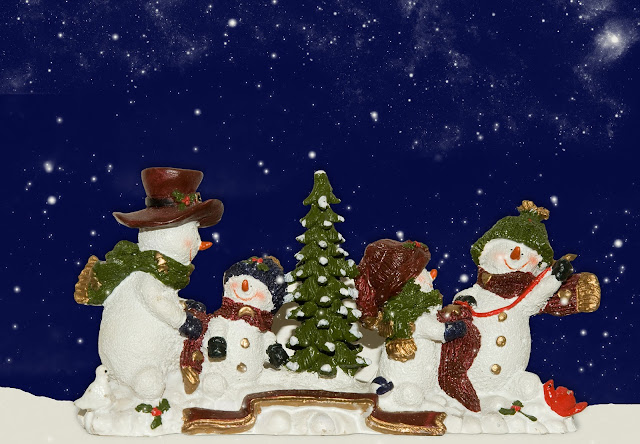 "Here's a family of snowpeople on a ""snowy"" base with starry background."