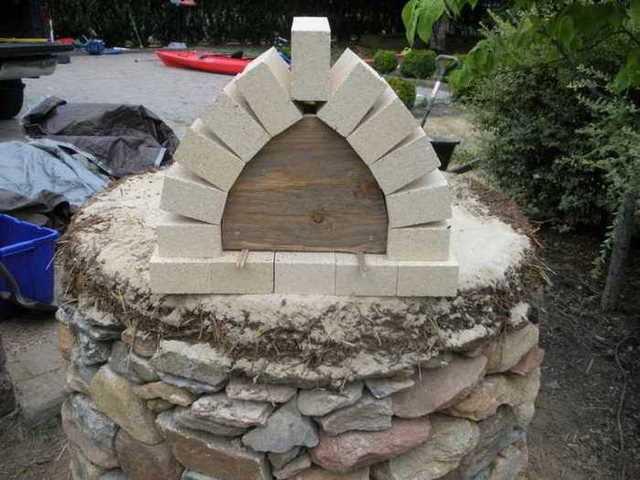 Segundo paso en la construcción del horno: rellenar con adobe y paja y preparar el arco de la puerta