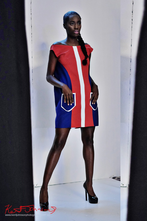 A model wears a bold red with navy blue dress with a white vertical stripe, patch pockets on the hips. André Bryson - Guerrilla - NYFW. Photographed for Street Fashion Sydney by Kent Johnson.