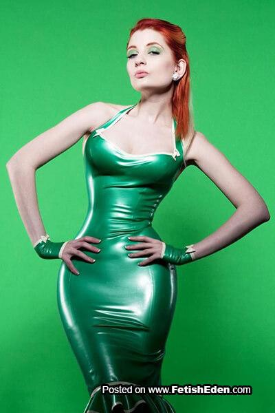 Beautiful redhead wears green latex dress and short green latex gauntlets