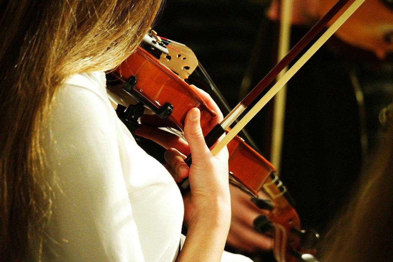 mulher jovem loira tocando violinho