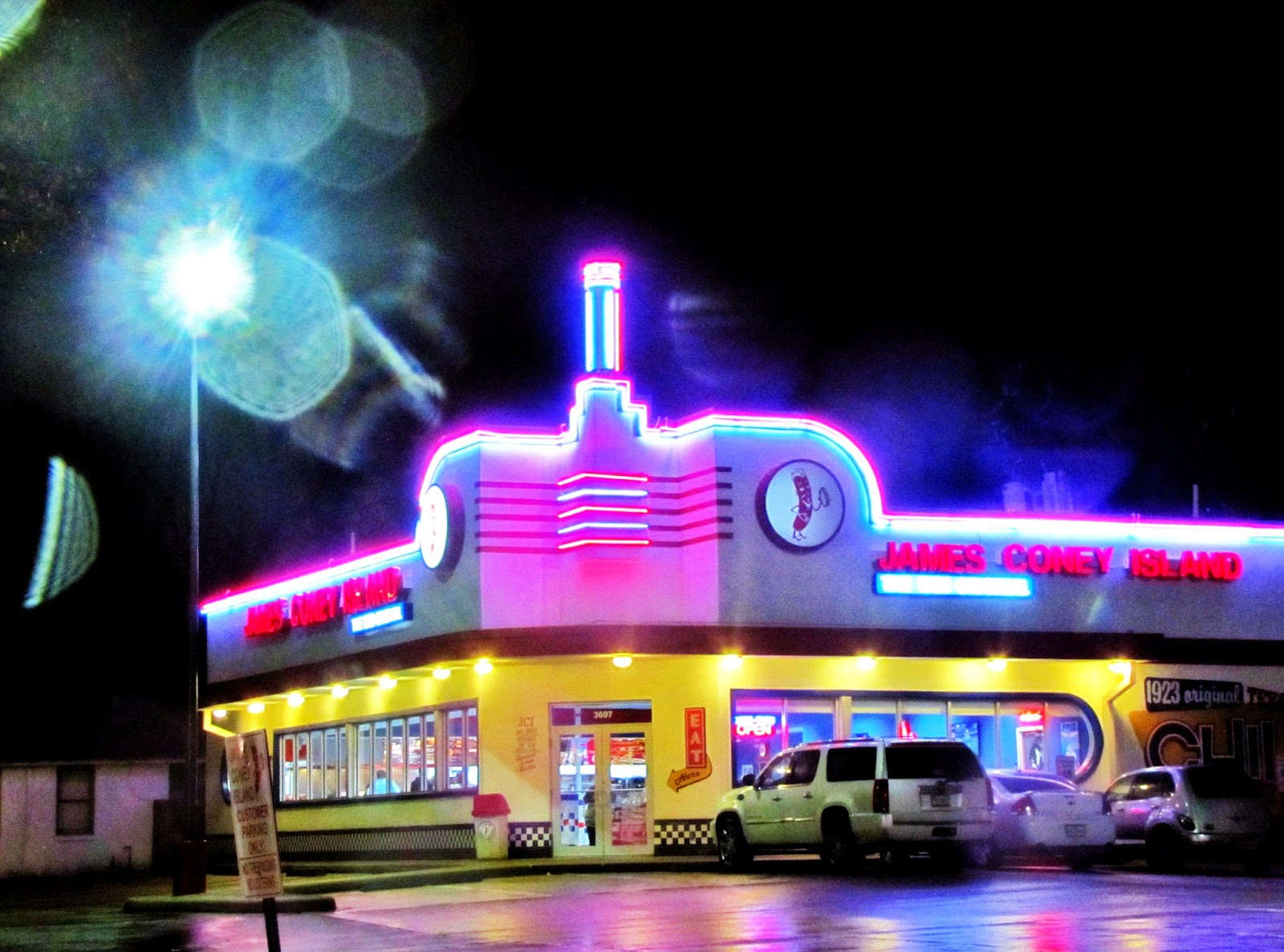 Night shot of Coney Island eatery with colorful neon signage and store lighting
