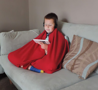 boy on blue sofa watching tablet videos