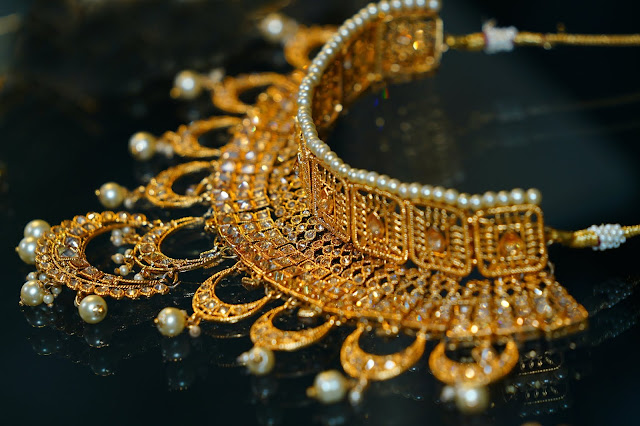 An intricate gold necklace laid out on display black marble.