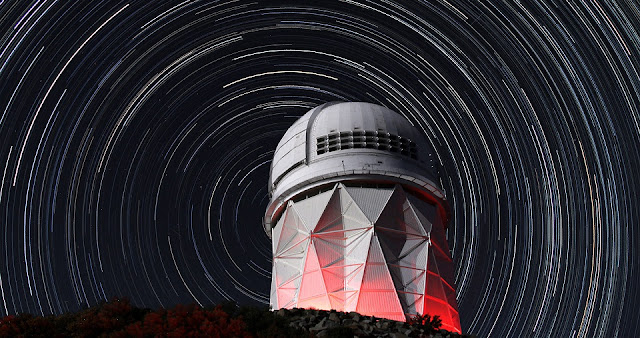 Star trails take shape around the 14-story Mayall Telescope dome in this long-exposure image. Installation of the Dark Energy Spectroscopic Instrument (DESI) will soon begin inside this dome. (P. Marenfeld/NOAO/AURA/NSF)