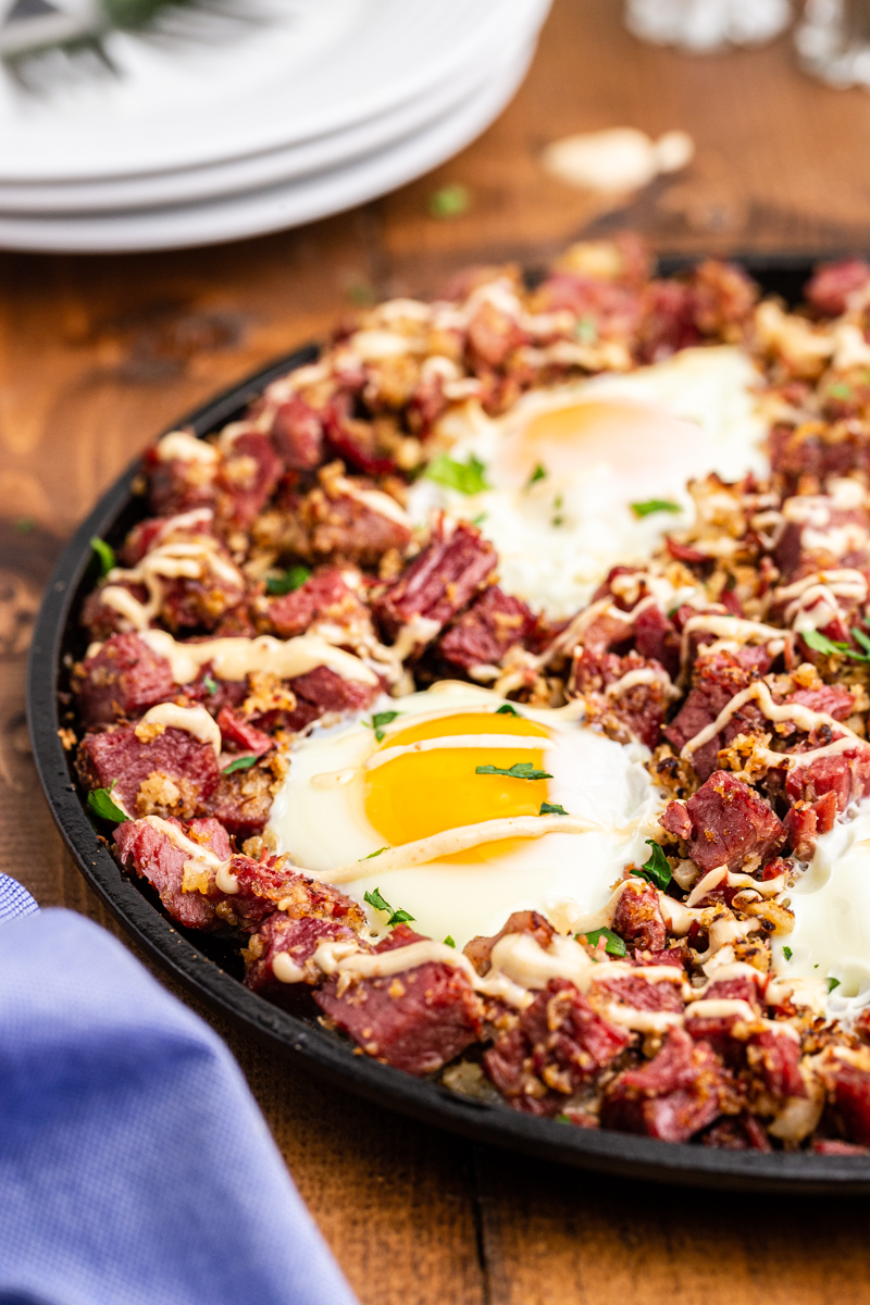 Closeup photo of Keto Corned Beef and Hash in a skillet on a wooden table.