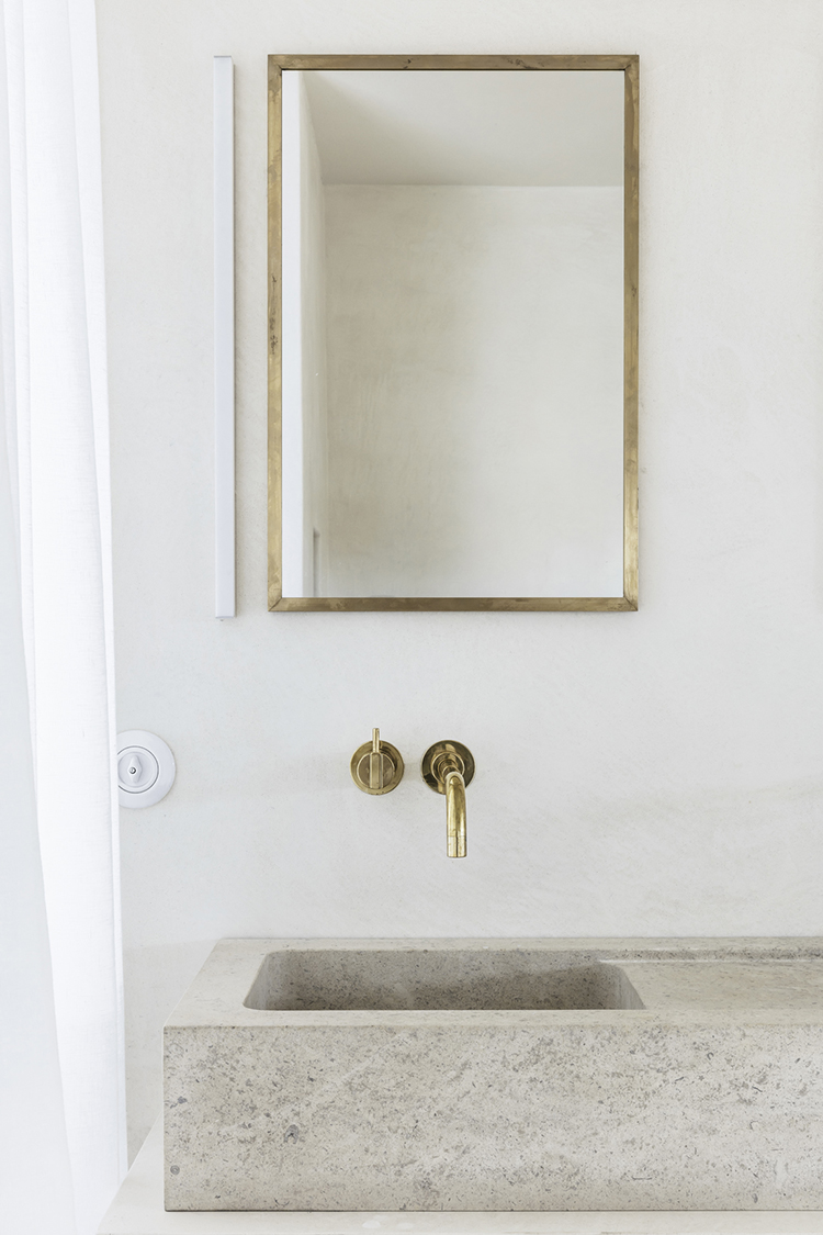 Bathroom with stone sink and brass fixtures. Interior design by Arjaan De Feyter, photo by Piet-Albert Goethals