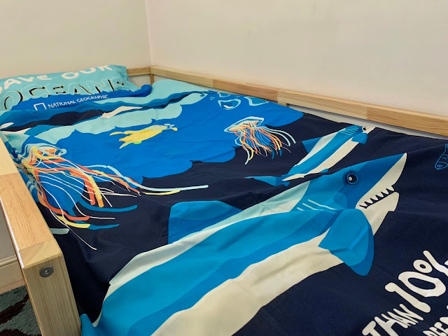 A duvet cover from National Geographic with Save Our Oceans written on the  pillow and a variety of sea creatures including a shark and 2 jelly fish on the duvet cover