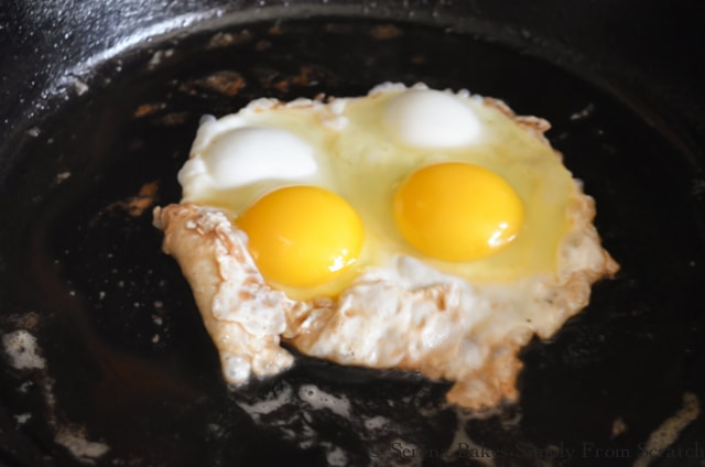 2 Eggs Frying in a Cast Iron Pan.