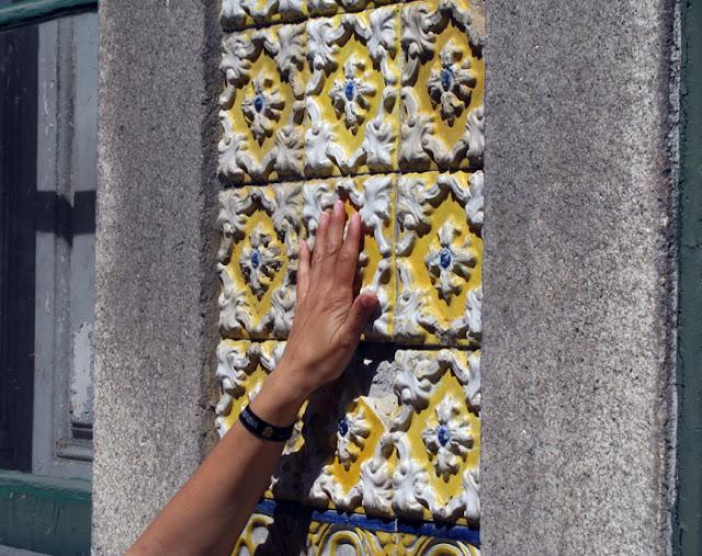 uma mão tocando nos azulejos do Porto