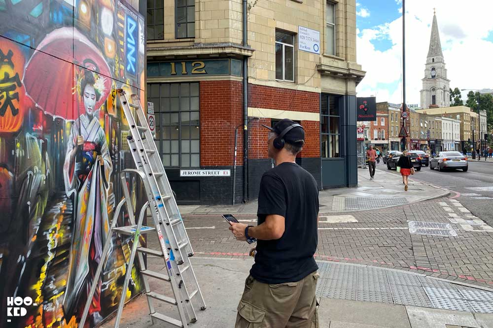 Dan Kitchener at work on his Geisha Street Art on Commercial Street, London