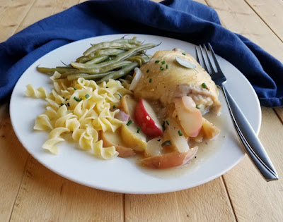 dinner plate with chicken and apples, buttered noodles and green beans, side view