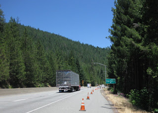 Semi truck passes cyclists riding on the shoulder of Interstate 5 approaching the Crag View exit near Dunsmuir, California