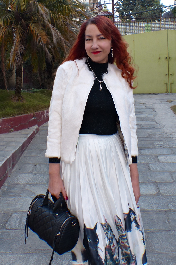 white fur jacket worn with satin pleated cat skirt