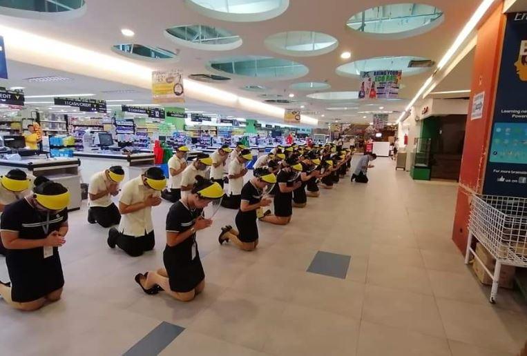 """""""We are frontliners too"""" Supermarket workers kneel down in prayer before work"""