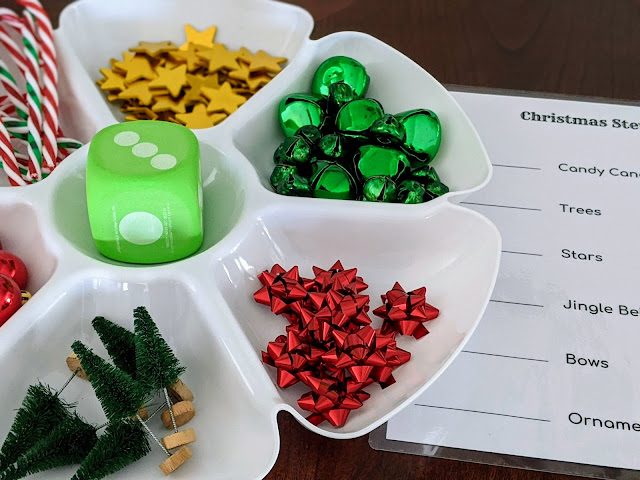 white divided tray with plastic candy canes, green jingle bells, red mini ornaments, gold stars, mini Christmas trees, green foam dice and red mini bows for counting math game
