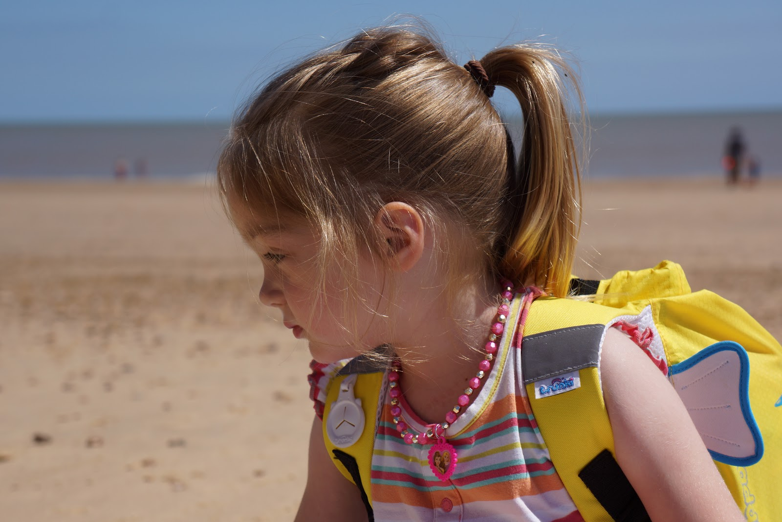 toddler girl at beach with Trunki swim bag