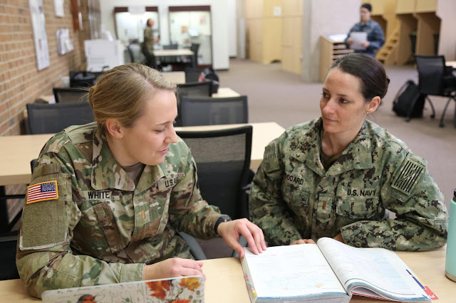 Army 2nd Lt. Paige White, left, and Ensign Cat Woodard, recently discuss an upcoming project.