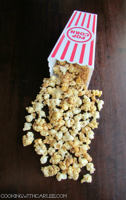 caramel corn spilling out of popcorn container laying on its side