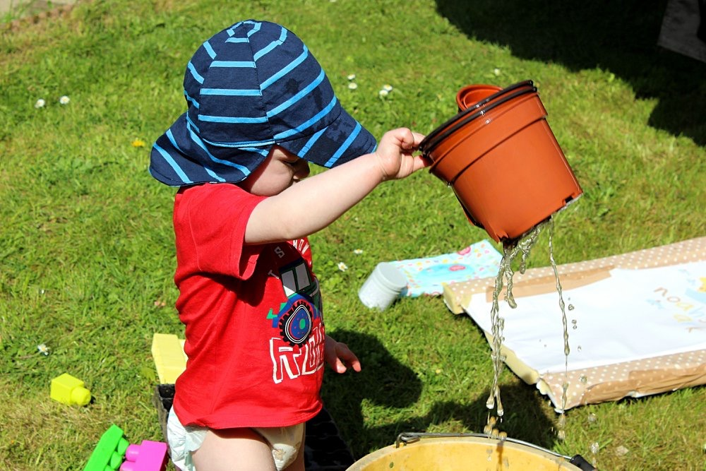 A small 1 year old boy wearing a red top and blue sunhat is holding up a plant pot as water pours out of it.