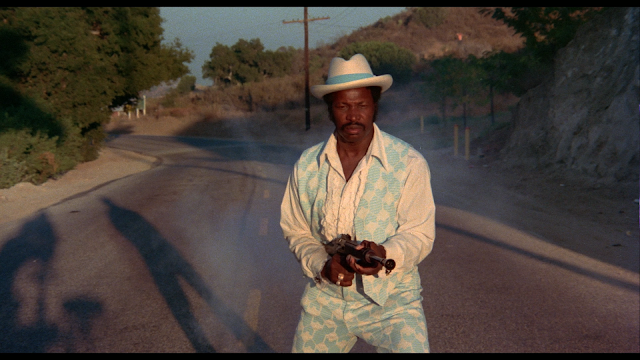 Dolemite shooting a gun while the camera crew's shadow is in the background