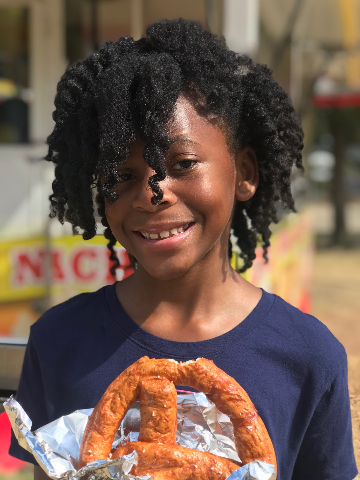 Image: Moriah Bell eating pretzel at carnival. Family Day Out: Soaking Up The Sun, Eating Junk Food And Capping Off Summer's End!