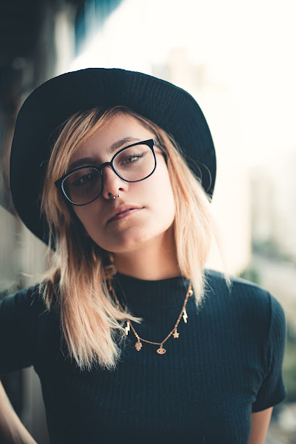Blonde woman wearing a necklace and hipster glasses.