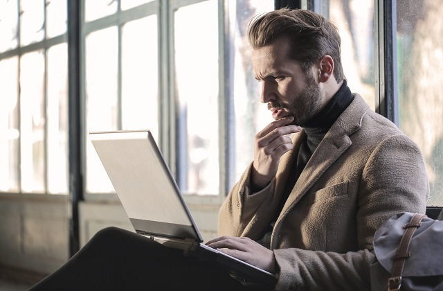 man in business attire looking at laptop confused