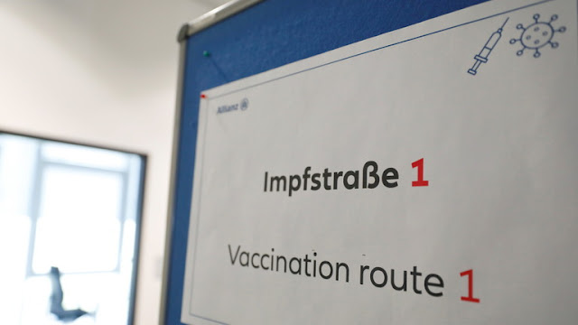 An informational panel hangs on the door at a coronavirus disease (COVID-19) vaccination centre at the Allianz Campus in Berlin, Germany, (FILE PHOTO) © REUTERS/Michele Tantussi