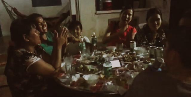 Keluarga Dieu mengelilingi meja sambil menyanyikan sebuah lagu secara bergiliran