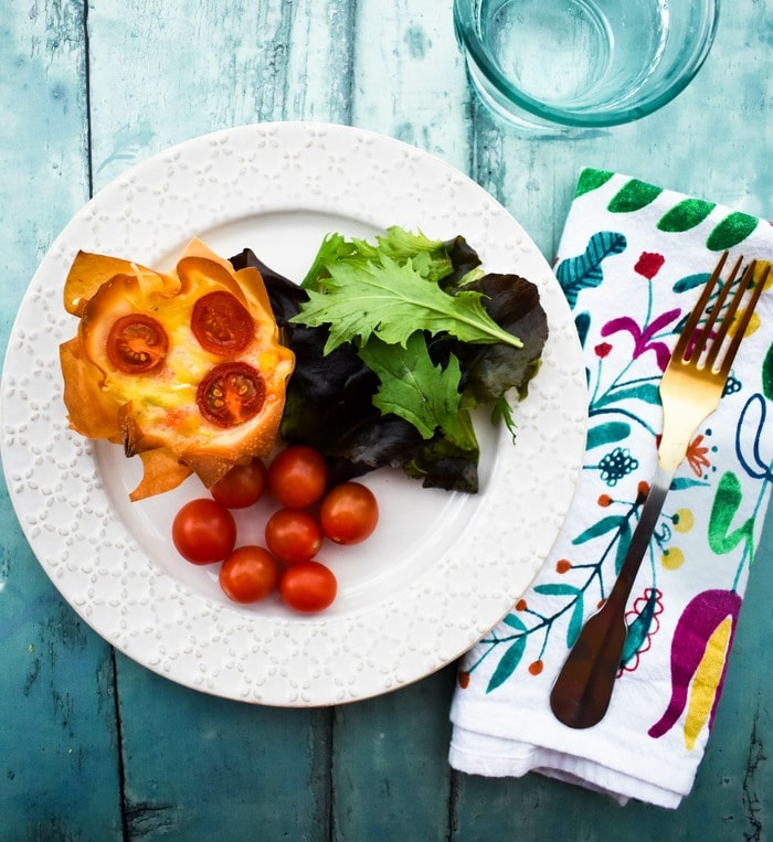 cheese and red pepper pies on a plate with salad